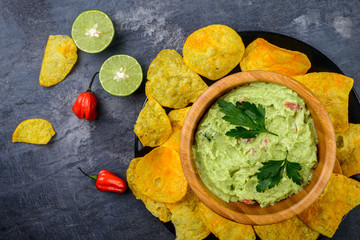 Guacamole with chips  on dark background, top view
