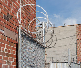 Warehouse security gate with circular barbed wire in urban area. Red brick building, blue sky and wispy clouds.