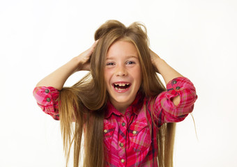 Young beautiful little girl smiles holding her hair over white background