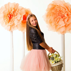 Young beautiful little girl with basket of flowers in leather jacket over white background