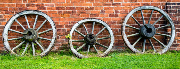 Three old wooden cart wheels against a red brick wall