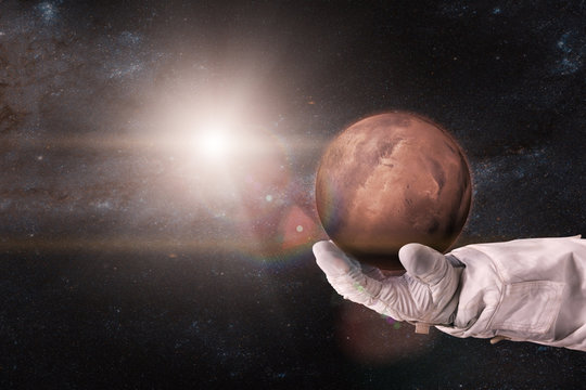 Mars in the hands of astronaut. Elements of this image furnished by NASA.
