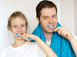 Father and his daughter brushing teeth in bathroom.
