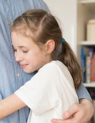 Happy little girl hugging her dad.