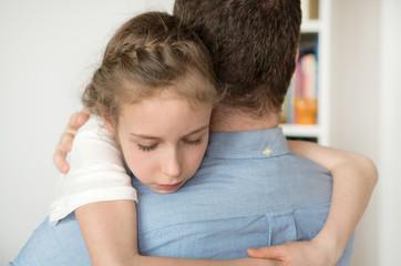 Sad little girl hugging her dad.