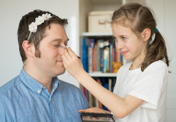 Cute little girl making makeup to her dad.