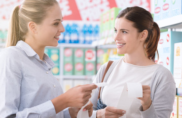 Women comparing grocery receipts