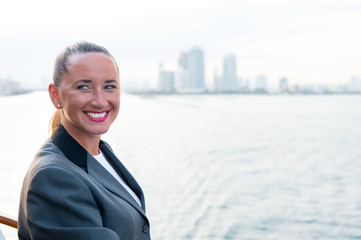 Sensual woman smile on ship board on city skyline. Woman in business jacket on shipboard in miami, usa. Fashion, beauty, look. Travelling for business. Wanderlust, adventure, discovery, journey