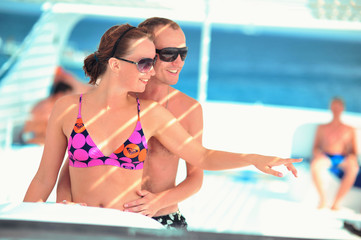 Happy young couple having beach fun on the yacht vacation honeymoon travel holidays. Caucasian woman and man playing playful enjoying love. Multiracial couple