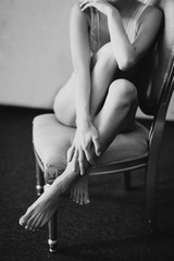 a girl in lingerie sits on a chair and hugs her legs
