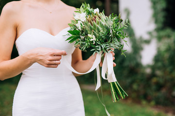 close-up of a bride's hand with a bouquet in a white dress that touches a bouquet is standing in a meadow