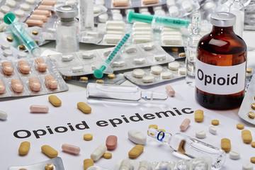 Eine Ampulle Opioid daneben liegt ein Zettel auf dem in Englisch Opioid Epidemie geschrieben ist. Drumherum liegen viehle tabletten und Spritzen verstreut.
