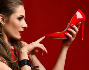 Beautiful brunette woman hold red shoe high hill on dark red