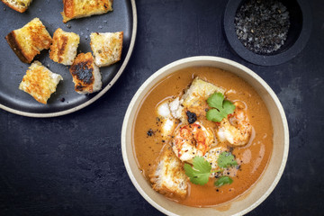 Traditional French fish soup with prawns and croutons at top view in a bowl