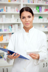 Medicine, pharmaceutics, health care and people concept - Smiling young pharmacist holding a clipboard and box of medications. Looking at camera