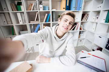 Handsome Caucasian teenage boy taking selfie and smiling joyfully while sitting alone in study room and doing homework