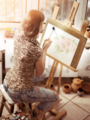 Artist painting on easel and palette in studio. Authentic girl paints with oil brush in morning sunlight dawn light toning window . Workshop of a professional artist. Back view drawing homework.