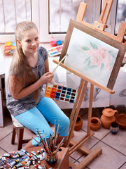 Artist painting on easel and palette in studio. Authentic girl paints with oil brush in morning sunlight dawn light toning window background. Drawing of spring flowers. Top view drawing homework.