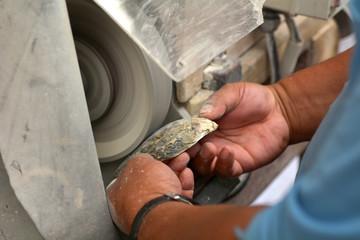 Hands of a Cook Islander man polishing  Tahitian Black Pearl shell Rarotonga Cook Islands