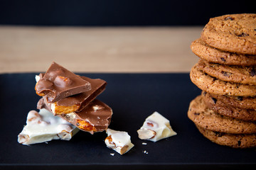 close-up of pieces of white and dark chocolate with nuts near a cookie on a black plate on a wooden table and on a black background