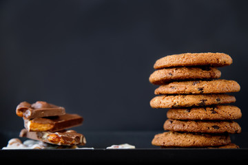 close-up of pieces of white and black chocolate with nuts and cookies on a black plate on a black background