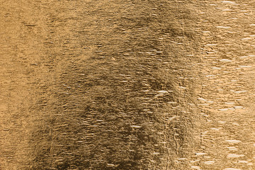 Gold foil yellow shiny metallic sheet surface texture as background
