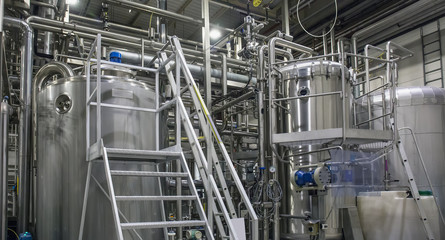 Stainless steel brewing equipment : large tanks and pipes in modern beer factory. Brewery production, industrial background