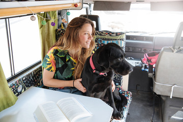happy young woman playing with her dog in a camper van