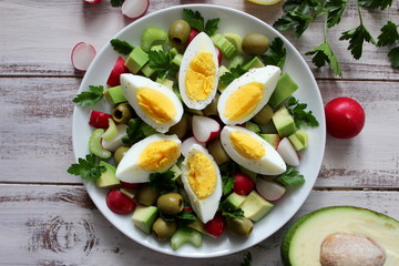 Healthy salad with olive, avocado, celery, raw and eggs on the plate. Top view.