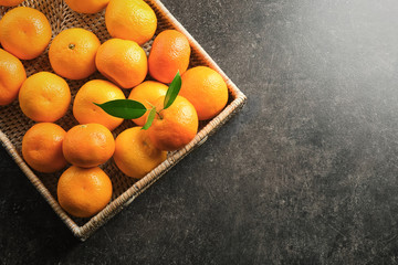 Wicker tray with juicy tangerines on table