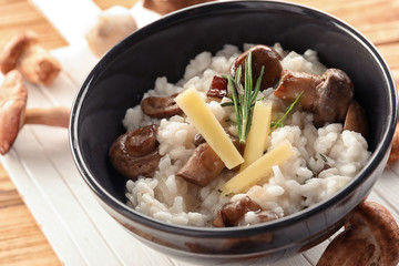 Bowl with risotto and mushrooms on table