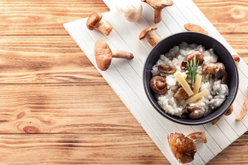 Bowl with risotto and mushrooms on wooden table