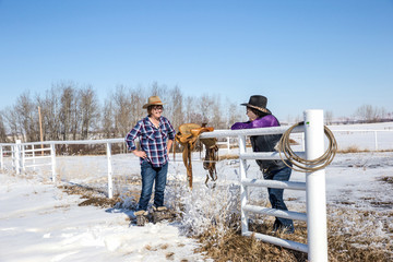 two ranching cowgirls chatting and laughing by the fence.