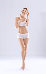 Young woman with beautiful silky body on  light background