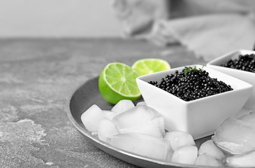 Black caviar served with ice cubes and lime on table