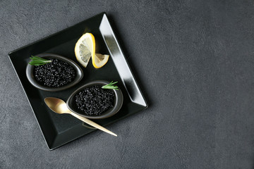 Bowls with black caviar on dark grey background