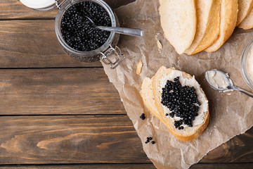Sandwich with black caviar on wooden background