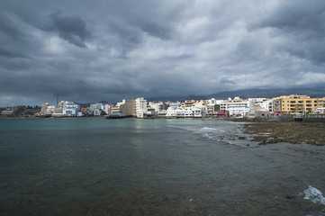 Dramatic overcast sky, low tide and calm waves in the town side of El Medano, Tenerife, Canary Islands, Spain