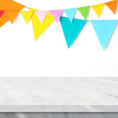 Colorful party flags hanging on white wall and white marble table background, birthday, anniversary, celebrate event, festival greeting card background