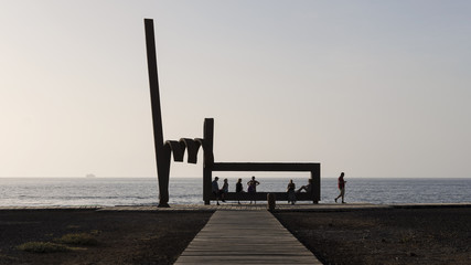 Silhouetted people resting or passing by the modernist iron sculpture at the beach of Las Americas