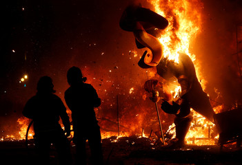 Firemen observe figures of a monument as it burns during the finale of the Fallas festival, which welcomes spring and commemorates Saint Joseph's Day, in Valencia