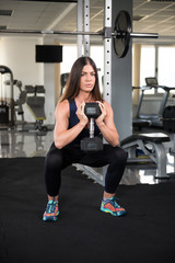 Woman Exercising Back and Legs With Dumbbells