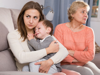 Two adult female are having disagreements with upbringing kid