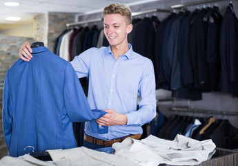 smiling man choosing jacket in the shop