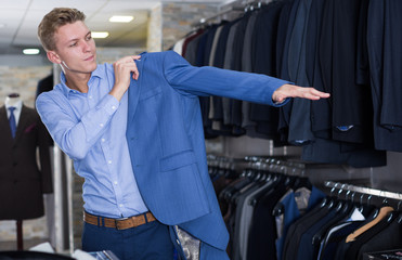 Adult male in suit trying  jacket in the store