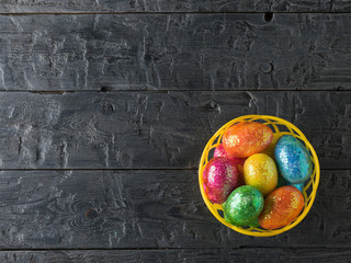 Basket with colorful eggs on a black rustic table. The view from the top.