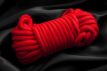 Hedonism, adult rope games and BDSM lifestyle concept with close up on a red soft ball of rope, used in the japanese erotic arts of kinbaku, sinju and shibari, on black silk