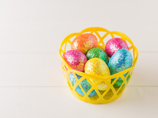 Yellow basket with colorful eggs on a wooden table.
