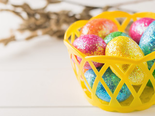 Basket with colorful eggs on a white wooden table.