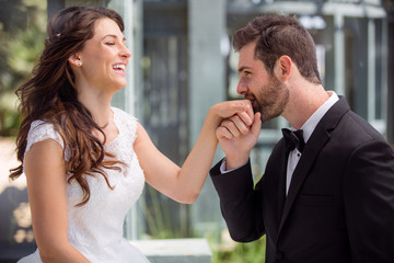 Groom and bride smile and share romantic moment kissing hand